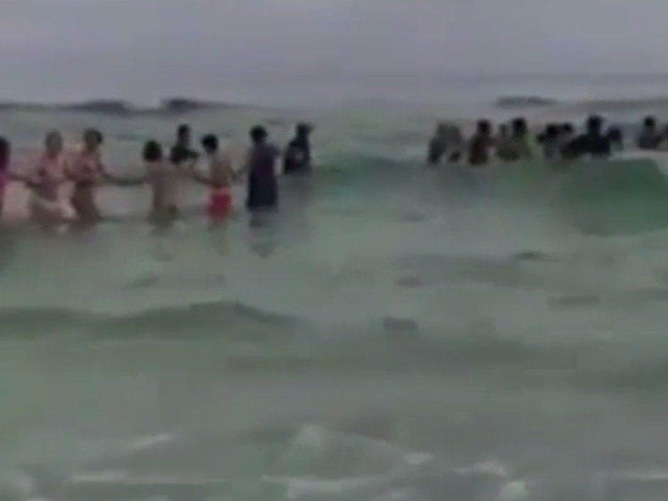 ¡Asombroso! Valla humana salva a nueve de ahogarse